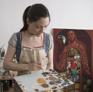 Madeline Von Foerster in her studio with her painting &quot;Amazon Cabinet&quot; in the background. 